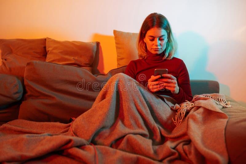 Fundersam damsittig med plädet på soffan Ung kvinna som använder mobiltelefonen, medan spendera tid hemma arkivbild