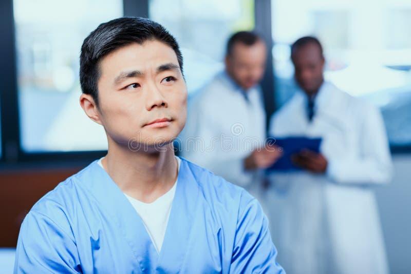 Fundersam doktor i medicinsk likformig med kollegor bakom i klinik royaltyfri foto