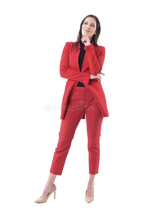 Fundersam elegant affärskvinna i den röda dräkten som ser tänka upp ha idé royaltyfria bilder