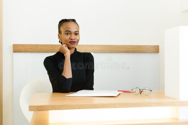 Fundersam elegant afrikan eller amerikansk affärskvinna för svart på skrivbordet i regeringsställning royaltyfria foton