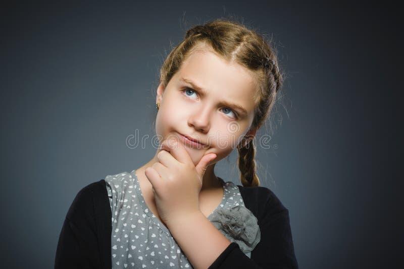 Fundersam flicka för Closeup med handen på huvudet som isoleras på grå färger arkivfoto