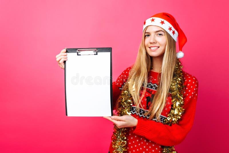 Fundersam flicka i en röd tröja och jultomtenhatt som rymmer en minnestavla royaltyfria bilder
