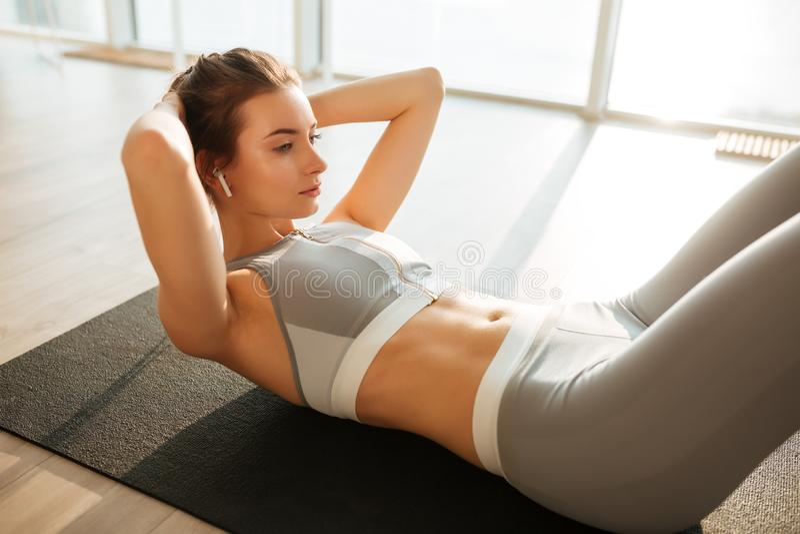 Fundersam flicka i sportig överkant och damasker som ligger på musik för press för yoga matt vagga lyssnande royaltyfri foto