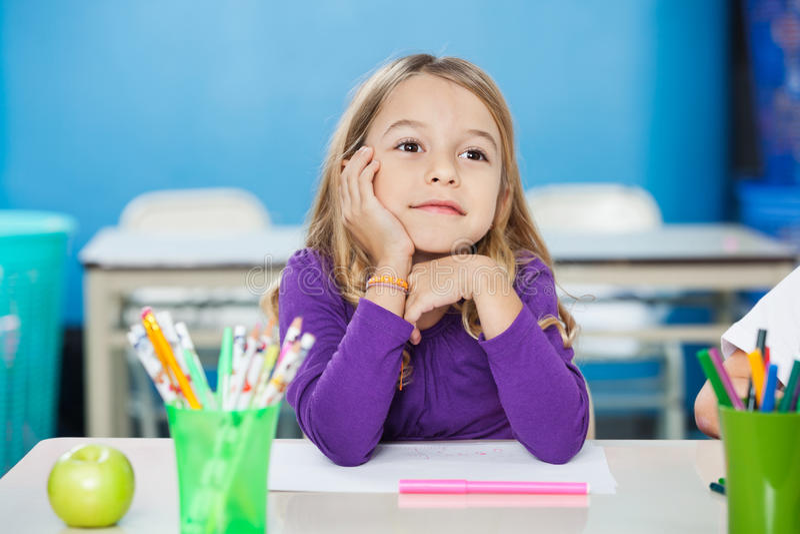 Fundersam flicka med handen på Chin Sitting At Desk arkivfoton