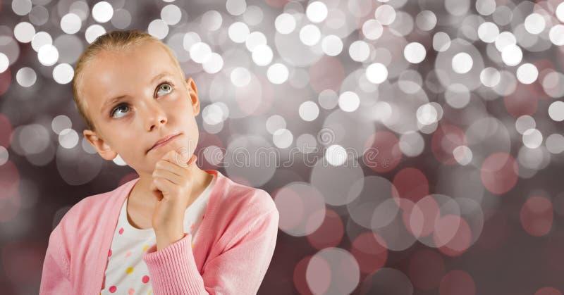 Fundersam flicka med handen på hakan över bokeh royaltyfria foton