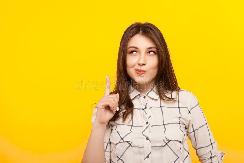Fundersam flicka som pekar upp arkivfoto