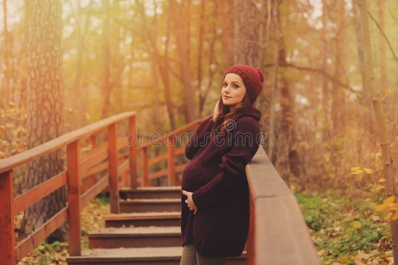 Fundersam gravid kvinna i mjuk varm hemtrevlig marsaladräkt som utomhus går royaltyfri fotografi