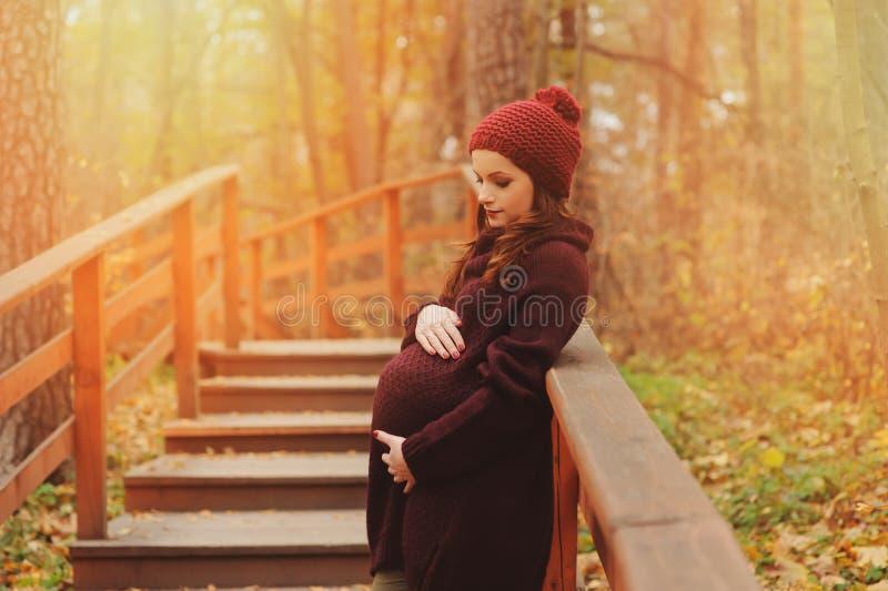 Fundersam gravid kvinna i mjuk varm hemtrevlig marsaladräkt som utomhus går royaltyfria foton