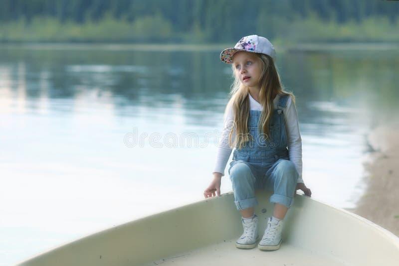 Fundersam gullig liten flicka i ett fartyg på sjön i ottan royaltyfri foto