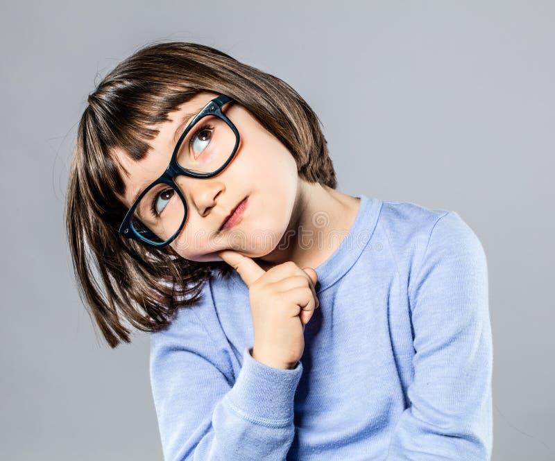 Fundersam härlig liten flicka med intelligent glasögon som ska föreställas arkivfoton