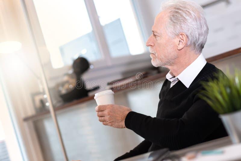 Fundersam hög affärsman som ser ut ur fönster arkivfoto