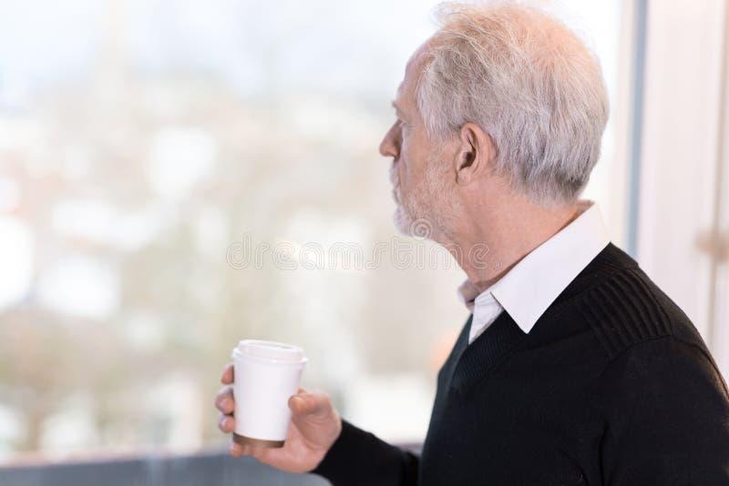 Fundersam hög affärsman som ser ut ur fönster arkivbilder
