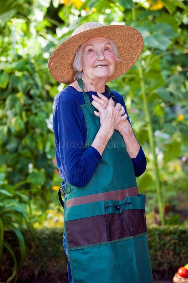 Fundersam hög kvinna i trädgårds- hatt och förkläde arkivfoton
