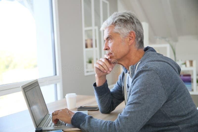 Fundersam hög man som arbetar på bärbara datorn arkivbild