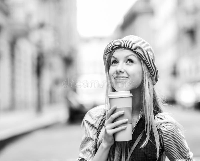 Fundersam hipsterflicka med koppen av den varma drycken på stadsgatan royaltyfri bild