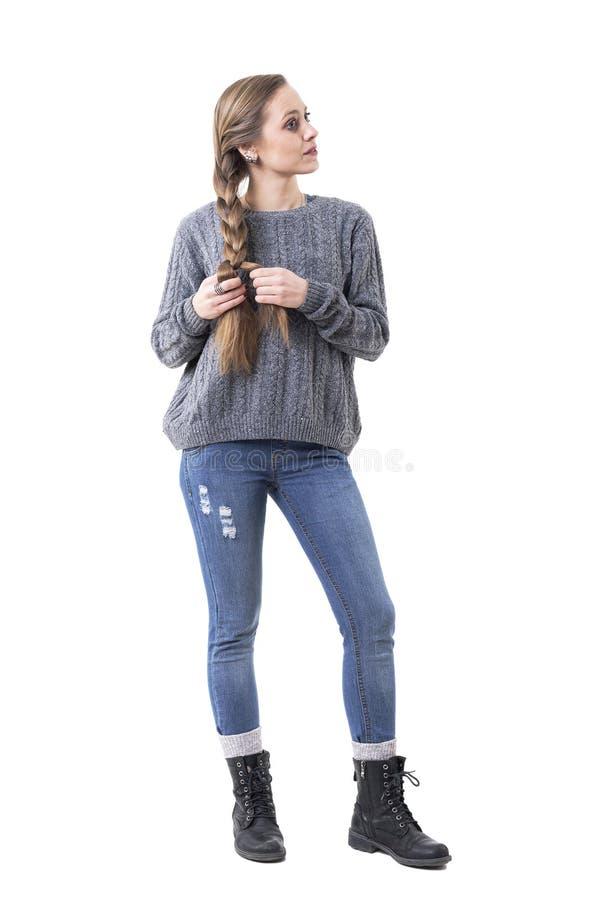 Fundersam introspektiv ung kvinna som gör flätade trådar för hår som bort ser royaltyfri fotografi
