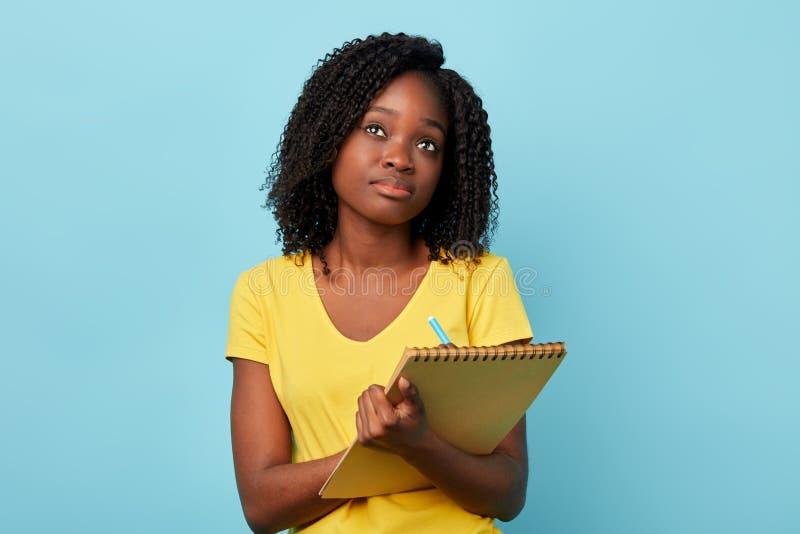 Fundersam koncentrerad upptagen härlig kvinna med notepaden som ser upp arkivfoton