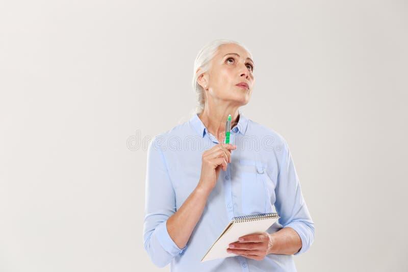 Fundersam kvinna med anteckningsboken och penna som tänker och ser upp royaltyfria foton