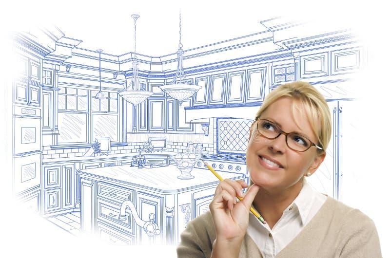 Fundersam kvinna med blyertspennan över beställnings- kökdesignteckning arkivbilder