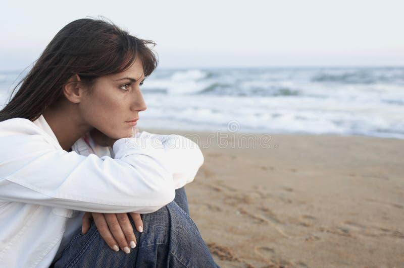 Fundersam kvinna som bort ser på stranden arkivfoton