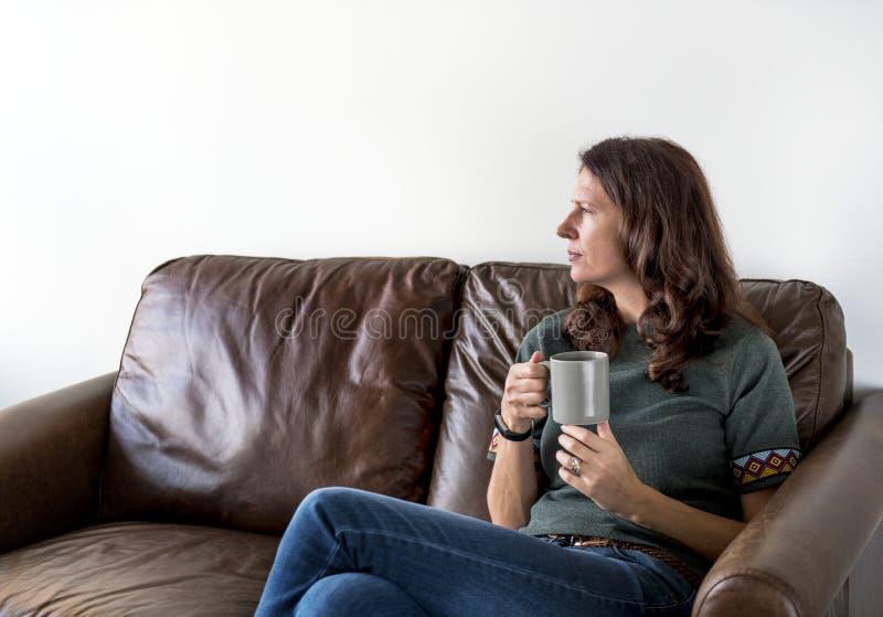 Fundersam kvinna som dricker te eller kaffe royaltyfri foto