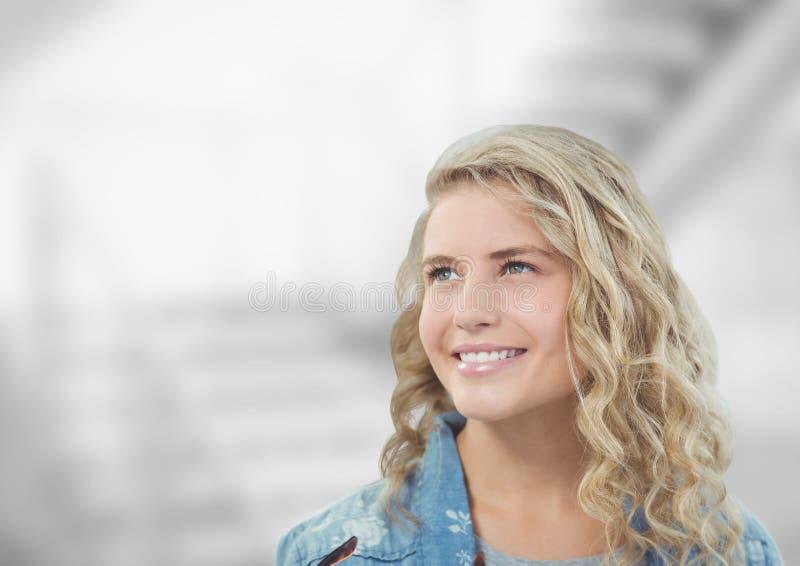 Fundersam kvinna som ler mot suddig bakgrund arkivbild