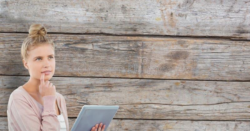 Fundersam kvinna som rymmer den digitala minnestavlan mot träväggen arkivbild