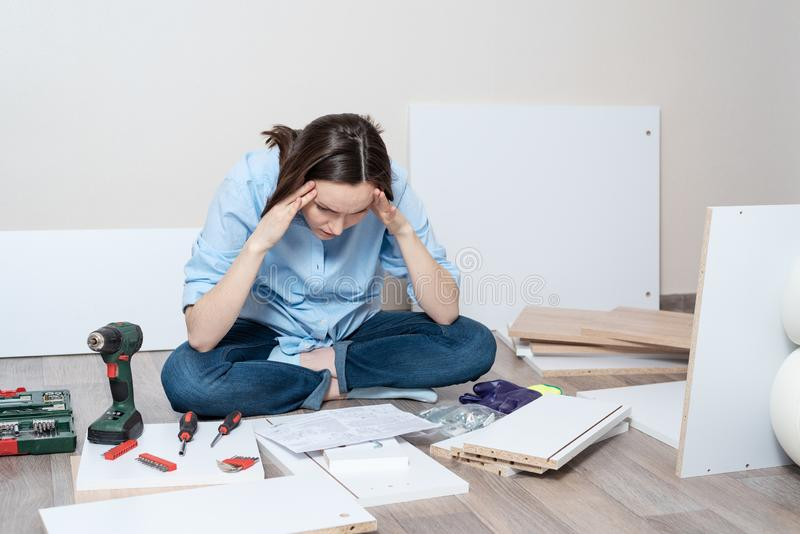 Fundersam kvinna som sitter på golvet för anvisningarna för enheten av möblemang arkivbild