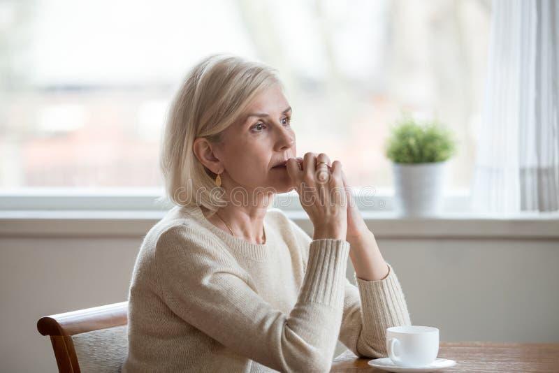 Fundersam kvinna som sitter på tabellen med kopp te royaltyfri fotografi