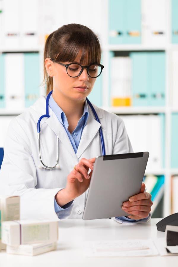 Fundersam kvinnlig doktor på skrivbordet genom att använda minnestavlan arkivbild