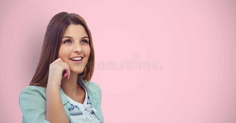 Fundersam kvinnlig hipster som ler mot rosa bakgrund fotografering för bildbyråer