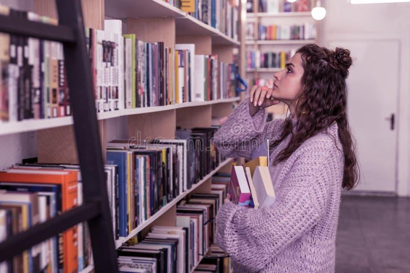 Fundersam långhårig kvinna i tröjan i storformat som trycker på hennes haka arkivfoto