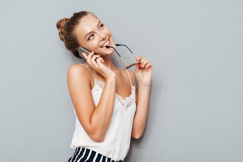 Fundersam le nätt ung kvinna som tänker och rymmer solglasögon royaltyfri fotografi