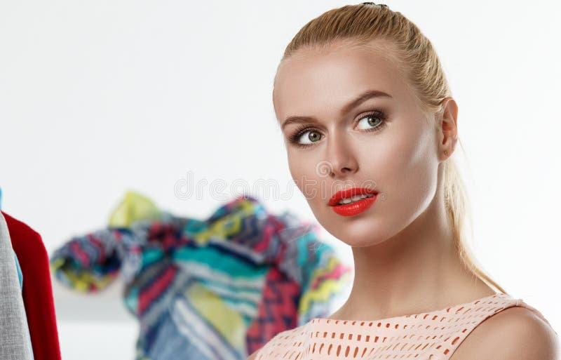 Fundersam ledsen härlig blond kvinna som står near garderobrac royaltyfri fotografi