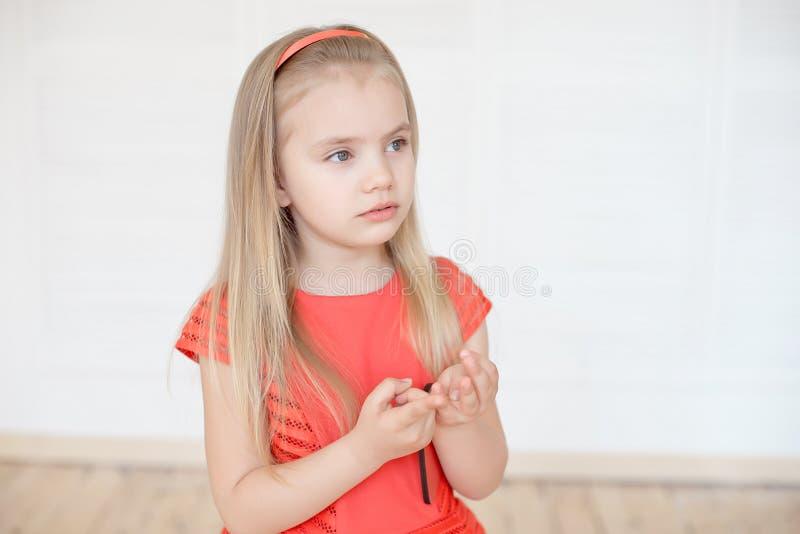 Fundersam liten caucasian flicka räkna henne fingrar inomhus royaltyfri fotografi