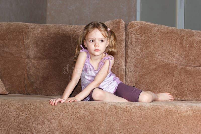 Fundersam liten flicka med råttsvansar som sitter på soffan arkivfoton
