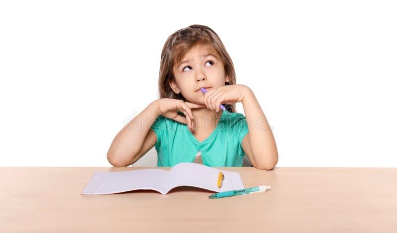 Fundersam liten flicka som gör läxa royaltyfria bilder