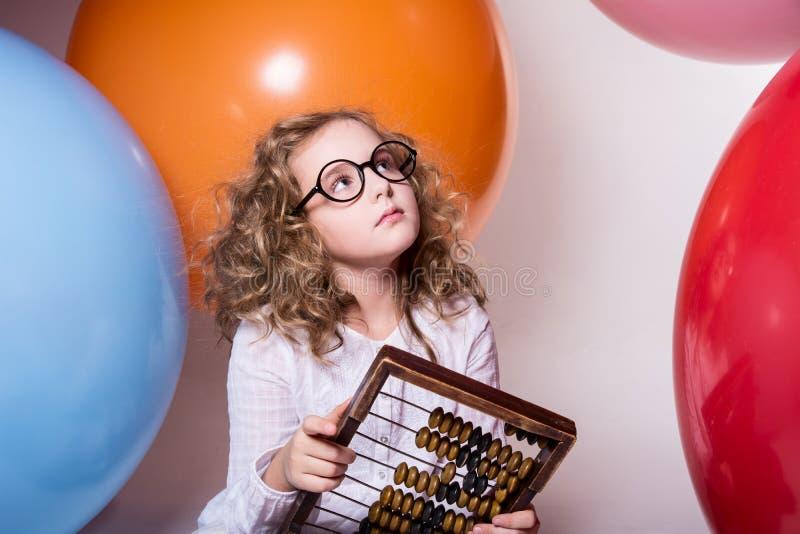 Fundersam lockig tonårig flicka i exponeringsglas med träkulrammet på royaltyfri fotografi