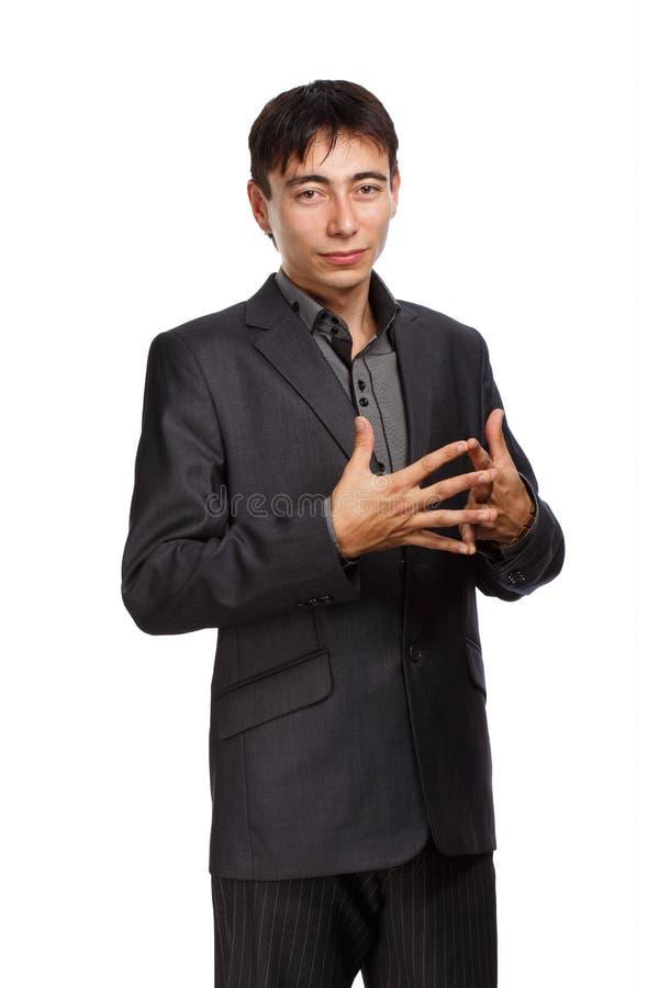 Fundersam man i mörk grå vardagsrumdräkt med flätade samman fingrar royaltyfri bild