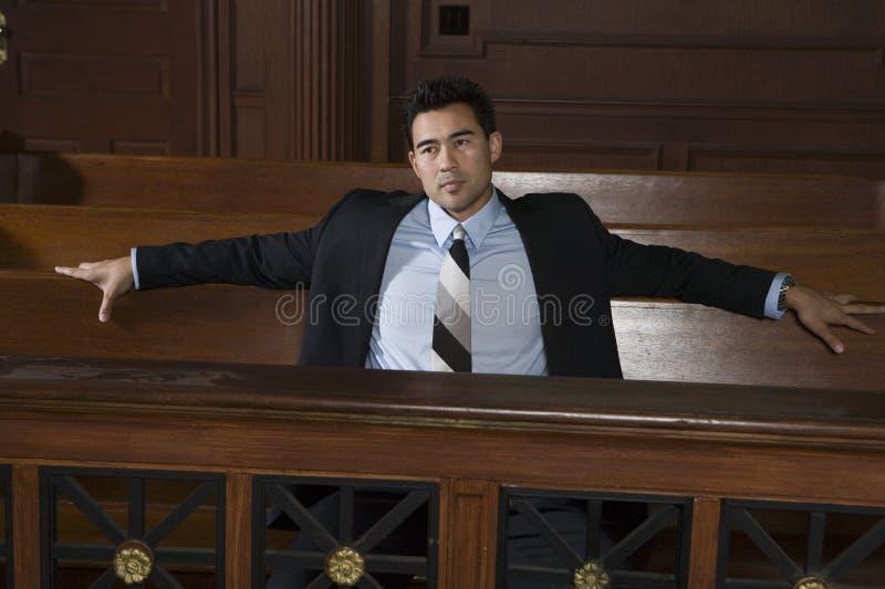 Fundersam manlig advokat Sitting In Courtroom fotografering för bildbyråer