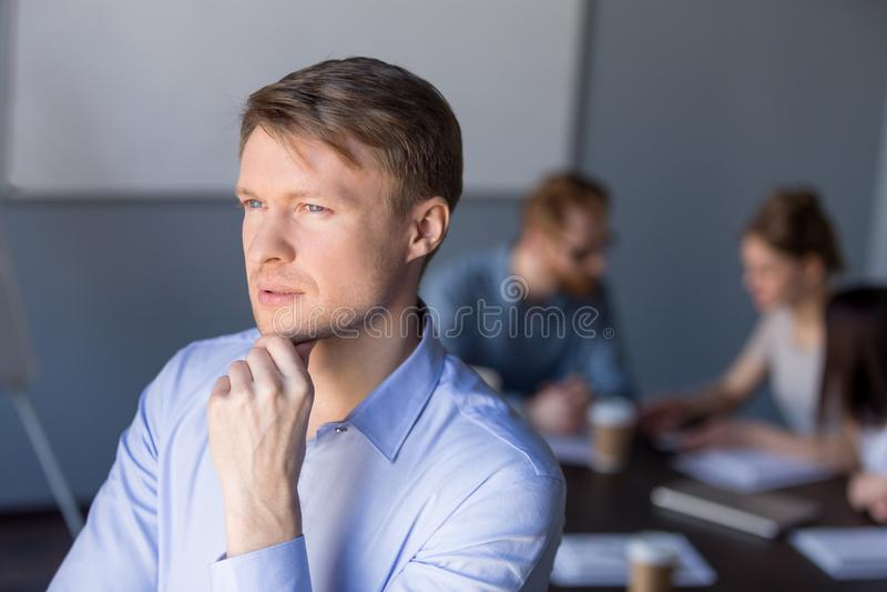Fundersam manlig anställd ser i avstånd som tänker om succes arkivbilder