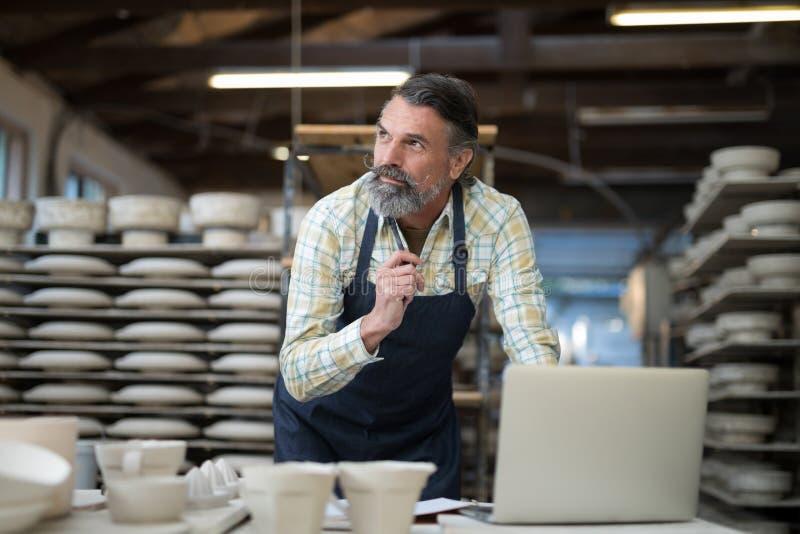 Fundersam manlig keramiker som arbetar på worktop royaltyfri bild