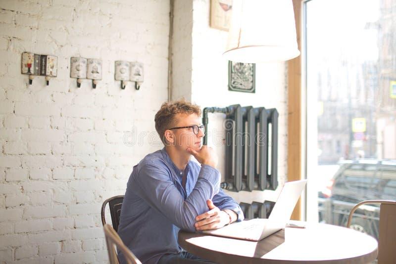 Fundersam manlig marknadsföringskoordinator som håller ögonen på i kaféfönster under arbete på netto-boken royaltyfri fotografi