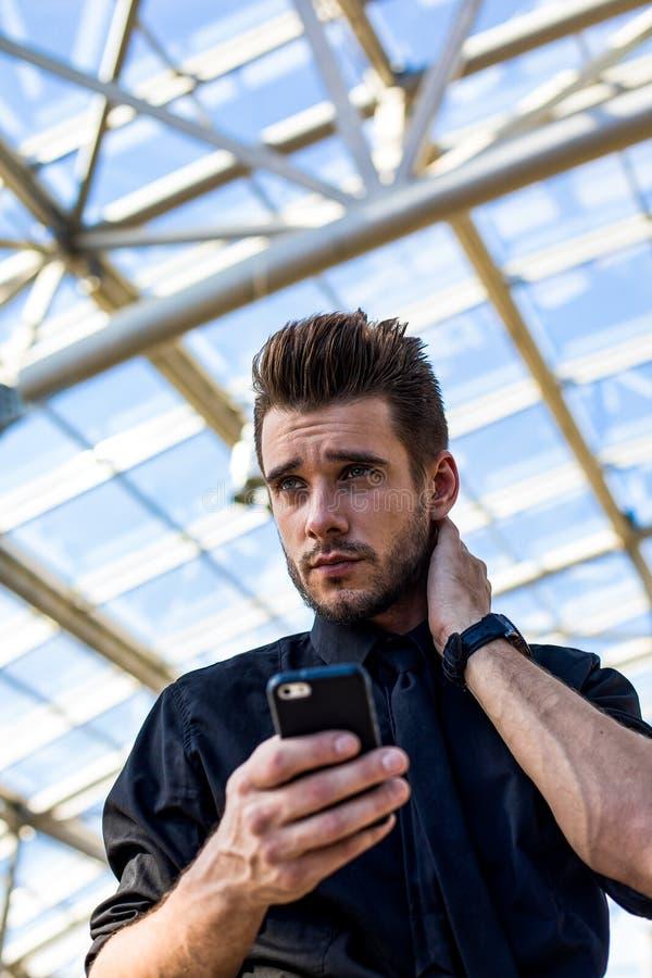 Fundersam manlig vd genom att använda applikationer på smartphonen som står i företag under lång arbetsdag arkivbild