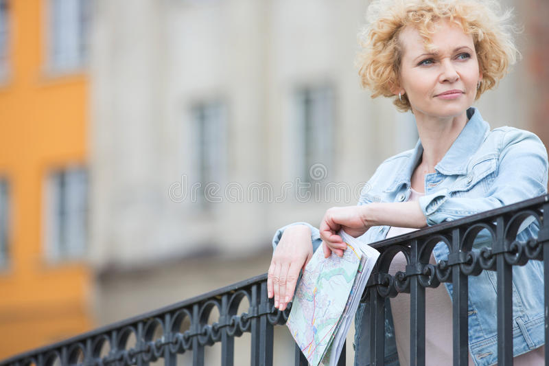 Fundersam medelålders kvinnainnehavöversikt, medan luta på räcket arkivfoto