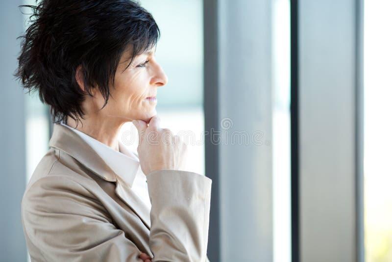 Fundersam medelåldrig affärskvinna arkivfoton