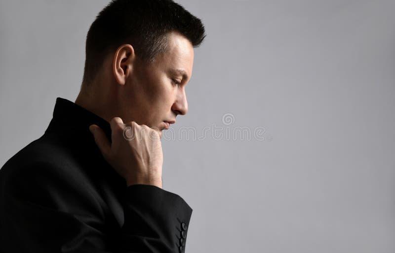 Fundersam modern man som från sidan står och ser ner turnes upp kragen av hans omslag royaltyfria bilder