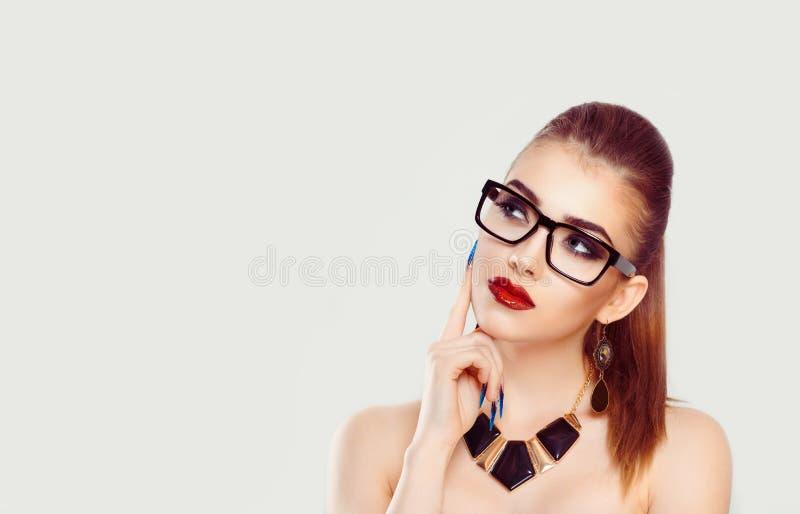 Fundersam person med glasögon som upp till ser sidan arkivbild