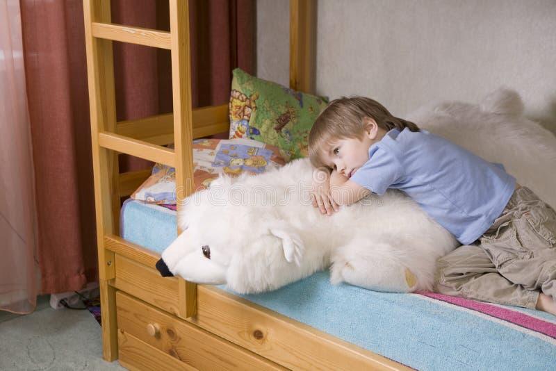 Fundersam pojke med mjuka Toy Lying On Bunk Bed royaltyfria bilder