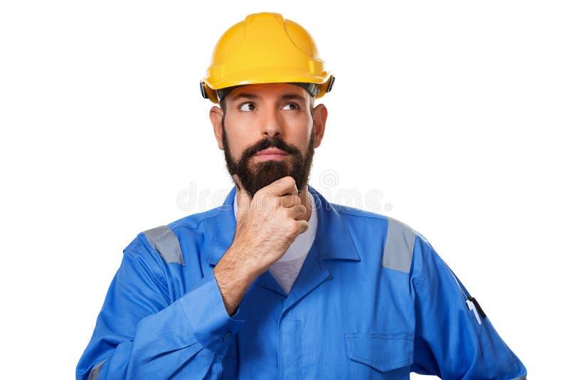 Fundersam skäggig mellersta ålderman i hård hatt, ordförande eller repairman i hjälmen som trycker på hans skägg och tänka som är fotografering för bildbyråer